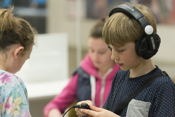 Photograph of a boy with headphones on