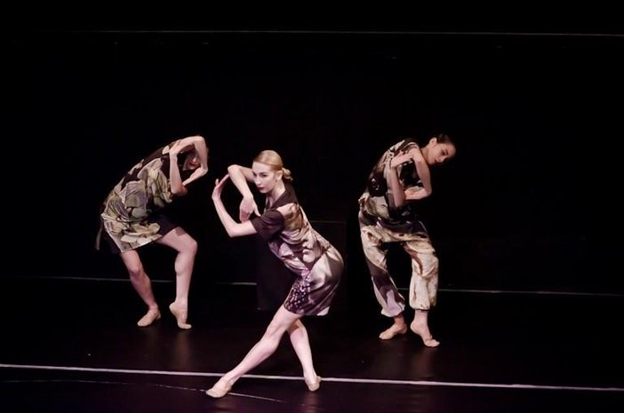 Three dancers do a contemporary dance on a blacked out stage