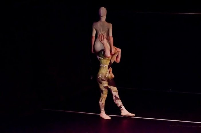A dancer sits on the shoulder of another dancer on stage