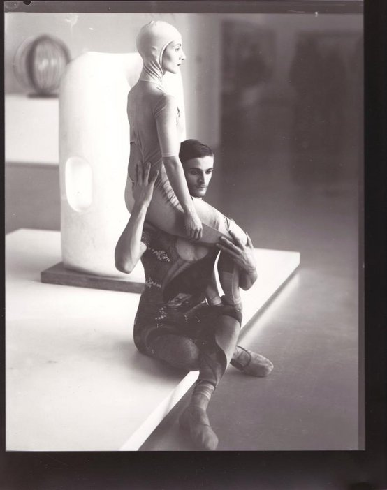 Black and white photograph of two dancers entwined sitting in a gallery setting
