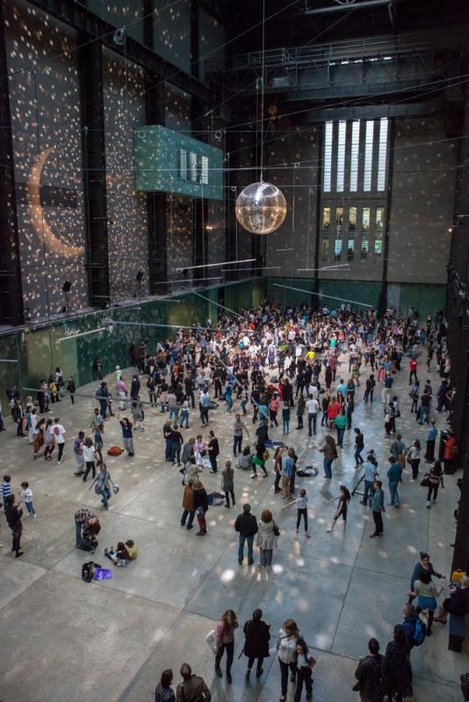 Disco ball and lights fills the turbine hall with dancers and visitors