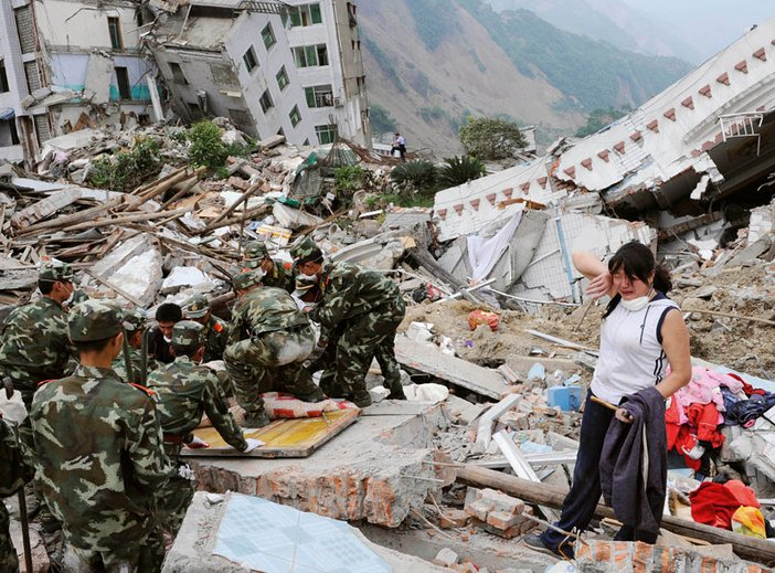 A woman stands amongst the debris of the earthquake in Sichuan Province South West China as rescue workers look for survivors May 2008