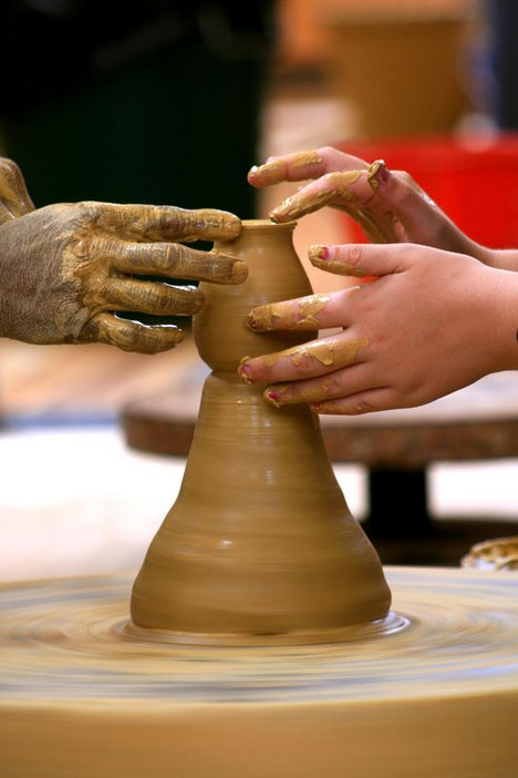 Image of hands on a pottery wheel