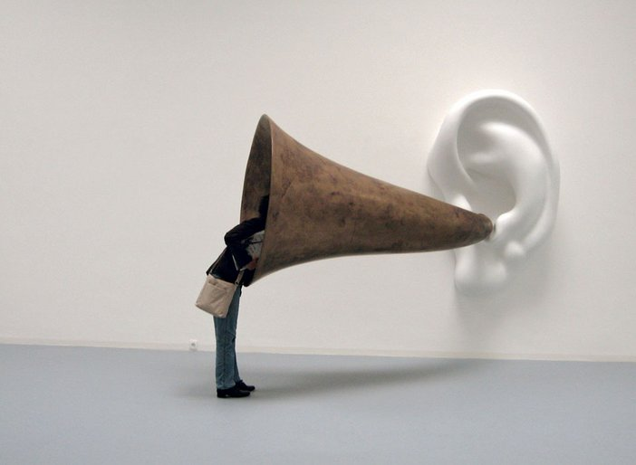 John Baldessari Beethovens Trumpet With Ear Opus 127 2007 a large white ear is mounted on the gallery wall with an ear trumpet attached a visitor has their head inside the trumpet