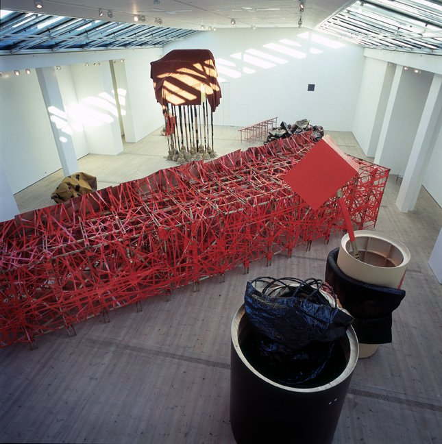 A view from above of the installation, the main object being a large red fretwork object