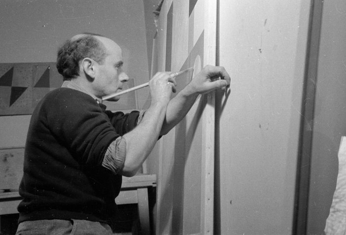 A black and white photograph of Ben Nicholson - he is working on a canvas