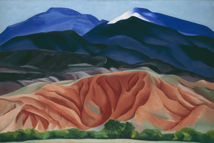 An oil painting of mountains in Mexico. The higher mountains are blue and the lower ones a peachy pink suggesting dessert