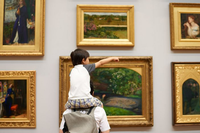 Father and son viewing artwork in Tate Britain's 1840 room
