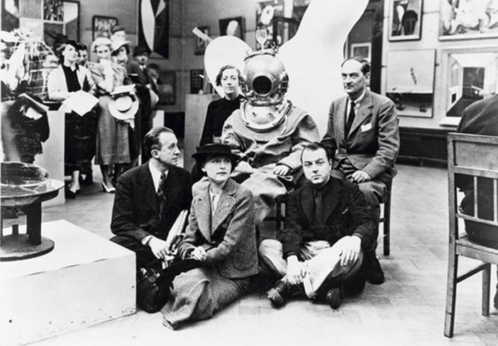 A black and white photograph of Diana Brinton-Lee, Salvador Dalí (in diving suit), Rupert Lee, Paul Éluard, Musch Éluard, ELT Mesens at the International Surrealist Exhibition in London (1936).