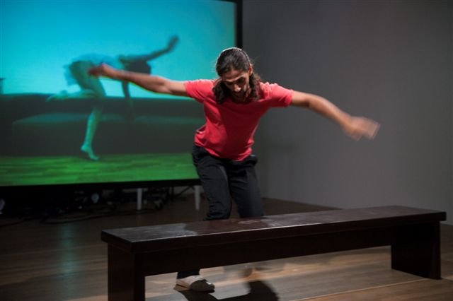 A performer in a gallery space with a projected image in the background