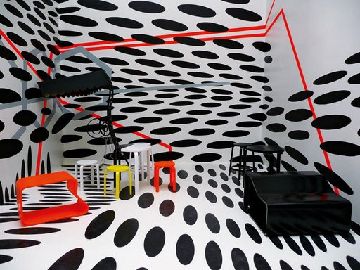 Cafeteria at the 53rd Venice Biennale designed by Tobias Rehberger 2009 photograph of an interior with floor to ceiling black and white spot pattern with minimal red yellow black and white furniture
