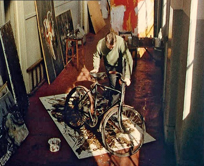 William Green using his bicycle tyres to spread liquid paraffin and black bitumen into the surface of the canvas, 1957