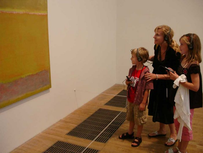 Children using a multimedia guide in front of a painting