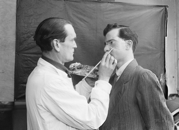 Captain Francis Derwent Wood RA of the Royal Army Medical Corps holds an artist's palette as he adds the finishing touches to a patient's new facial plate, photo by Horace Nicholls, c1914–8