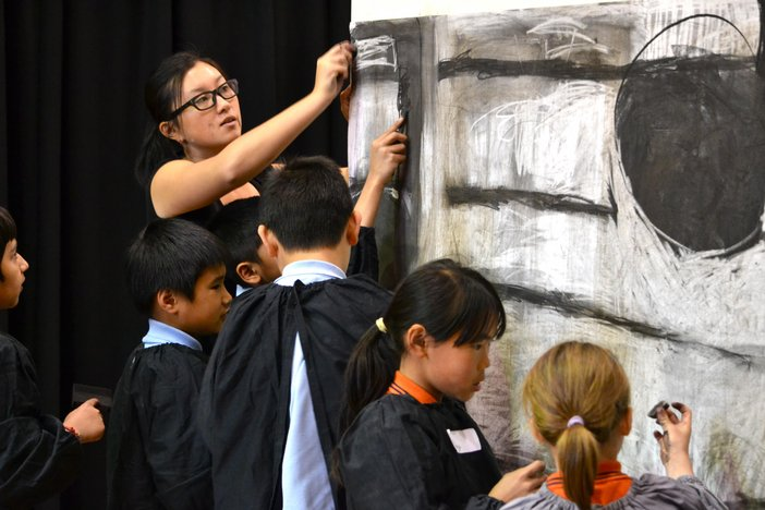 A group of children drawing in a workshop by Zhen Chew
