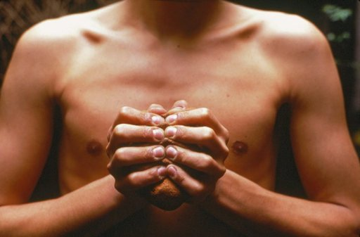 Gabriel Orozco My Hands Are my Heart 1991 photograph of a mans bear chest with his hands squeezing a peice of clay
