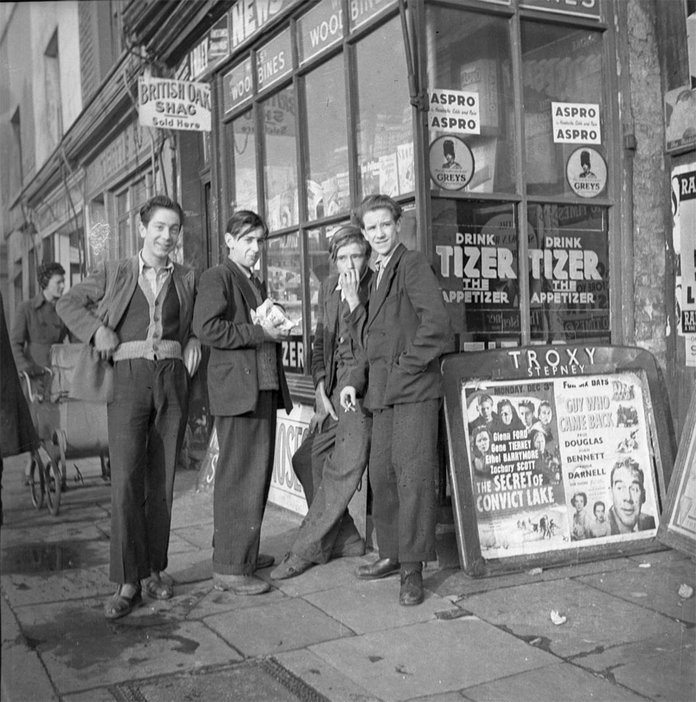black and white photograph of four men outside a shop in East London around 1951