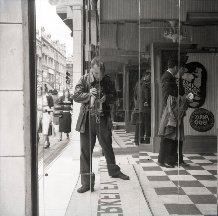 Black and white photograph of Nigel Henderson taking a picture of himself in a mirrored wall by a busy street