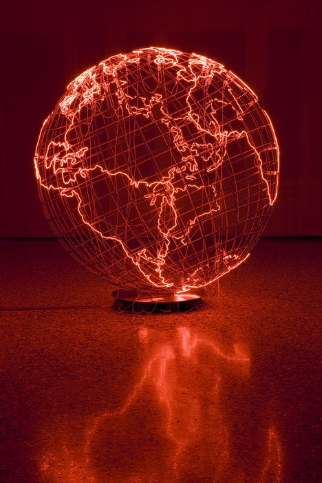Wire globe with areas of land marked out by thin, red, neon tubes.