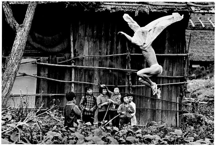 Black and white photograph of man jumping semi naked