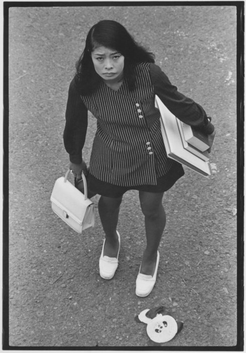 Black and white photo taken from above of Asian woman looking sad carrying an armful of books.