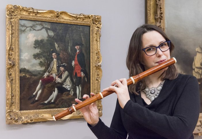 Hannah French poses with a replica of a baroque flute in front of Thomas Gainsborough's Peter Darnell Muilman, Charles Crokatt and William Keable in a Landscape c.1750