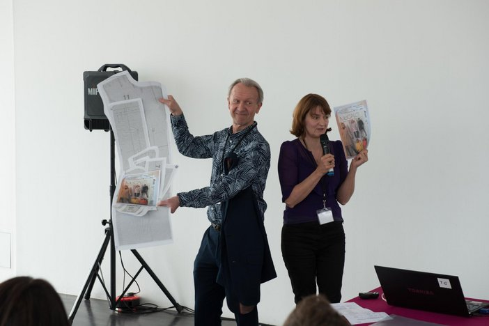 Two people presenting to a group hold up two pieces of paper