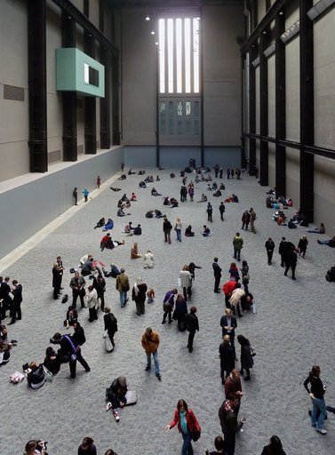 Installation view of Ai Weiwei Sunflower Seeds 2010 at Tate Modern interior view of the Turbine Hall with the floor covered in porcelain sunflower seeds and visitors walking over them