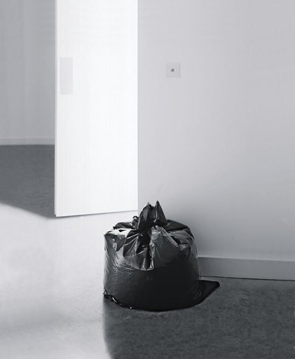 Installation view of Ceal Floyers Garbage Bag at Ikon Gallery Birmingham 2001 photograph of a black bin bag against a white gallery wall
