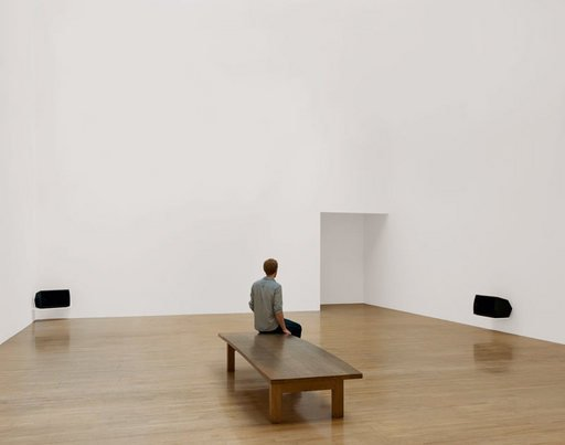 Installation view of Turner Prize winner Susan Philipszs Lowlands at Tate Britain October 2010 photograph of a white gallery with two audio speakers and a visitor sat on a bench