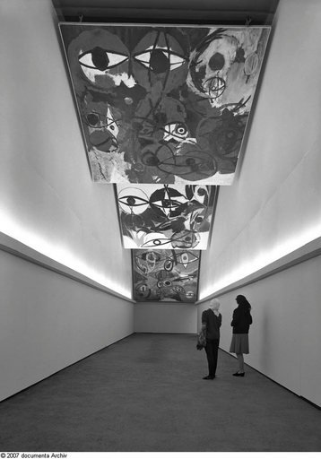 Installation view of works by Ernst Wilhelm Nay at Documenta 3 in Kassel curated by Arnold Bode 1964 photograph of a hallway with paintings hung from the ceiling