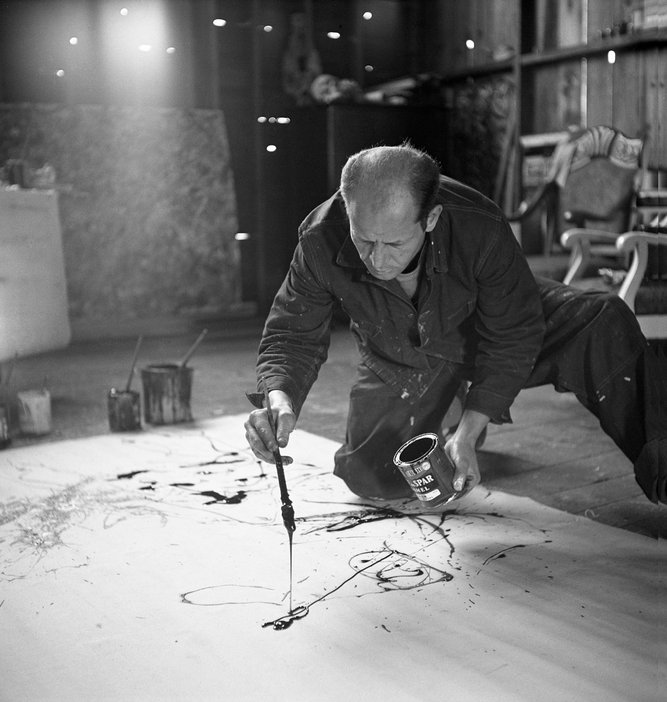 Painter Jackson Pollock working in his studio, dropping paint onto canvas