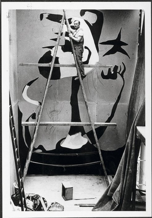 A black and white photograph of Joan Miró working on his mural The Reaper in the Spanish Pavilion at the Paris World Fair in 1937 .