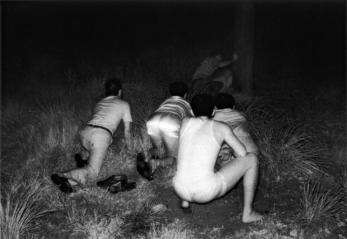 Kohei Yoshiyuki untitled 1971-1979 from the series the park a photograph of men crouched down surrounded by grass