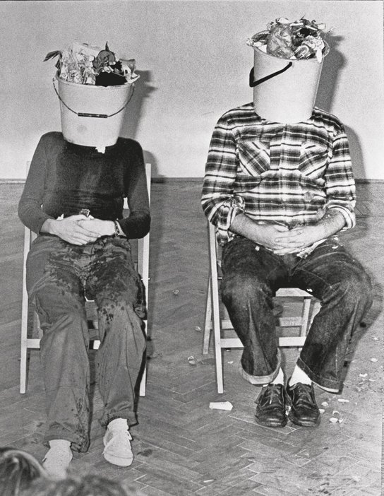 KwieKulik Activities with the Head 3 Parts still of a performance with two seated figures with buckets over their heads
