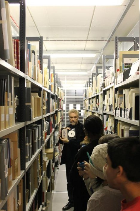 A member of Tate's archive leads a group around the archive, showing an item