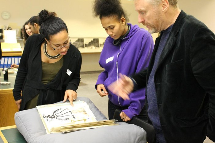 Three visitors look at an opened sketchbook in Tate's archive