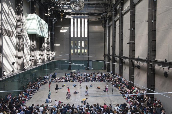 Crowd sit around the turbine hall with some dancers in the middle