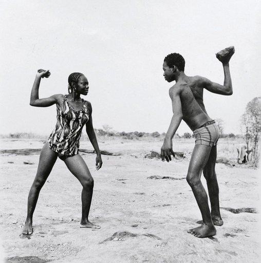 Malick Sadibe Friends Fighting with Stones 1976 black and white photograph of a male and female figure set in the African countryside each holding a stone above their heads and facing one another