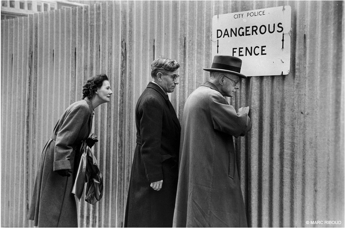Marc Riboud, London (1954). Three people peering through a fence