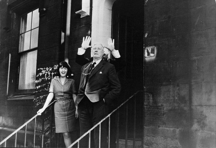 Carol Lowry, L S Lowry and Micky Marshall (behind) on the steps of the Stone Gallery, Newcastle, 1968