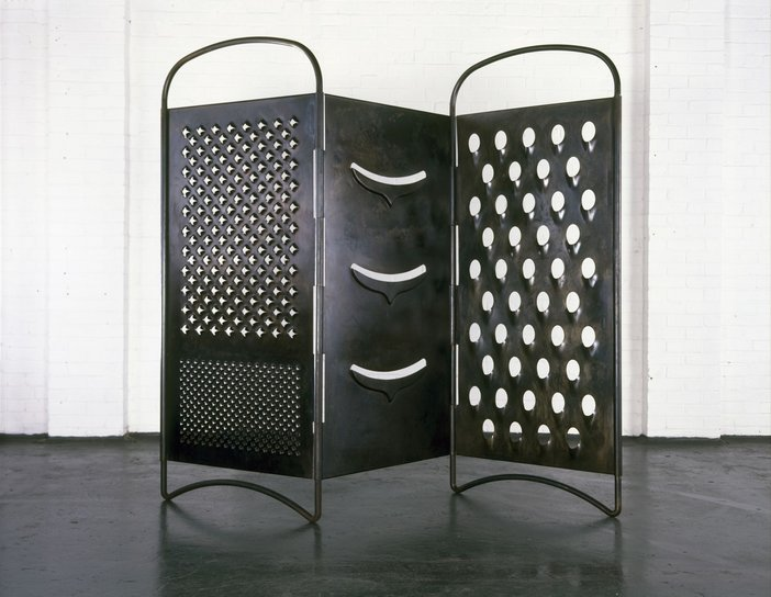 A large screen, like those used in hospitals, made out of metal with sharp holes in it like a giant cheese grater