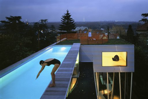 Office for Metropolitan Architecture Villa DallAva 1991 Colour photograph of a woman diving in to a pool and a man standing on grass on the rooftop of a contemporary house