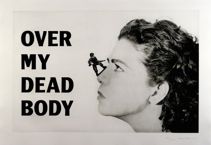 A poster image in black and white shows a womans profile with an army figure sat on her nose. The text says 'Over my dead body' in black capital letters