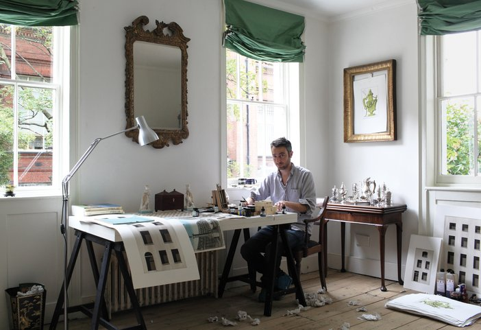 The artist Pablo Bronstein sitting at a table at his home