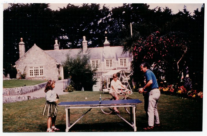 Peter Lanyon and daughter Anna Mary playing table tennis, with son Matthew on bicycle, at Little Park Owles, Carbis Bay c.1960