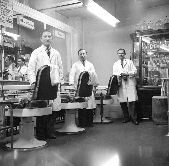 black and white photograph of three men inside a barber shop circa 1949 - 1956