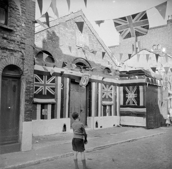 black and white photograph of a boy in a street covered with bunting, for Queen Elizabeth's coronation in 1953