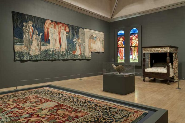 Pre-Raphaelites: Victorian Avant-Garde Installation view showing carpet, tapestry, book, stained glass and William Morris's bed