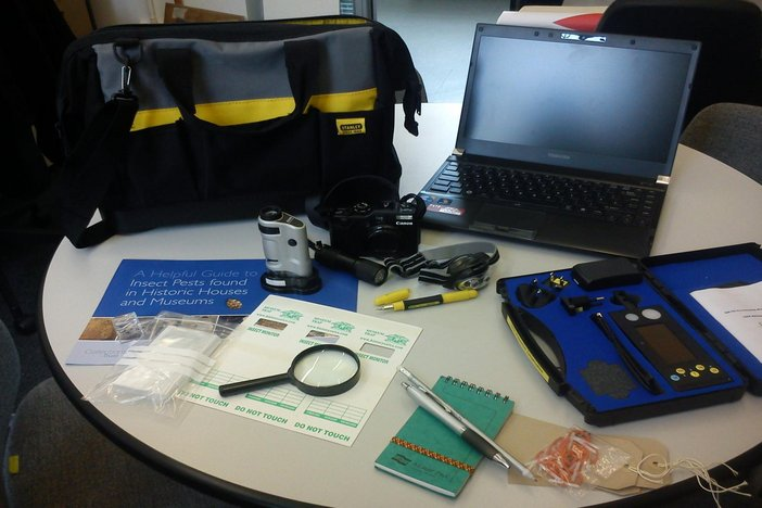 Conservative Science preventive kit is laid out on a table including laptop, readers and notebooks